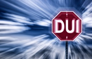 Stop sign against a moody sky with the letters DUI printed on it. Image is blurred to imply motion blurred vision due to intoxication.